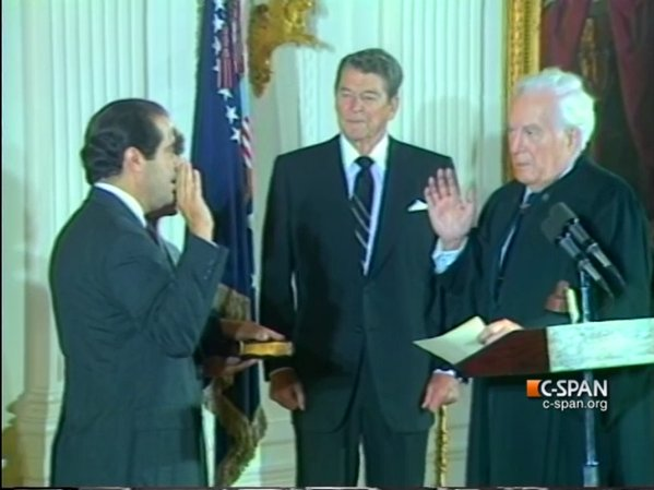 Antonin Scalia (left) being sworn into the Supreme Court as former president Ronald Reagan (center) watches