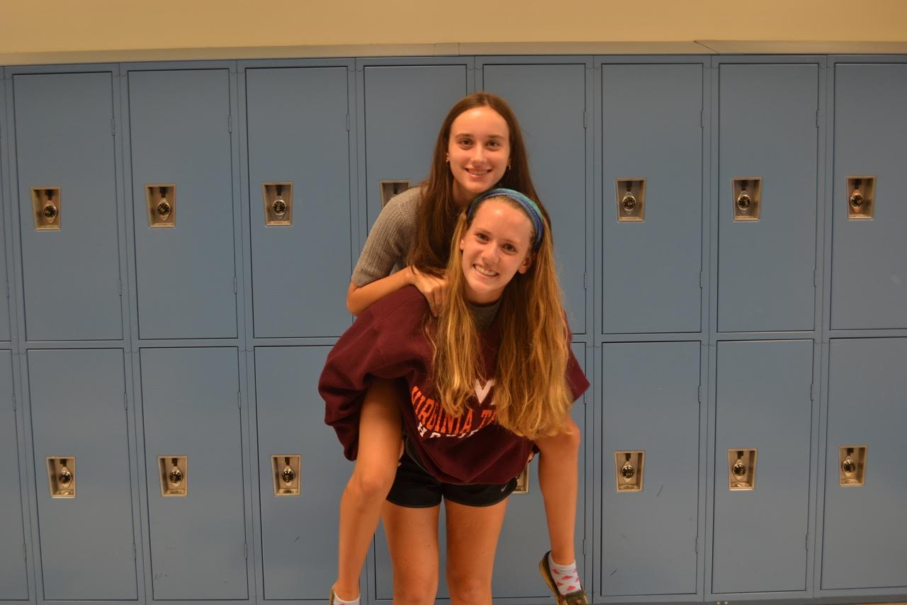 Emily Calvert and Sophie Dalton giving piggy-back rides for the camera.