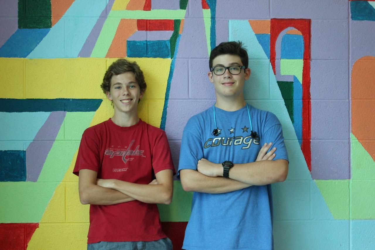 Topher Wagner and Charlie Schiavo pose boldly in front of a colorful painting.