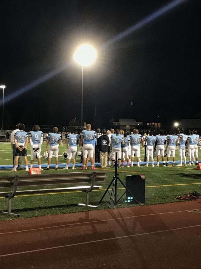 Yorktown's football team stands for the National Anthem