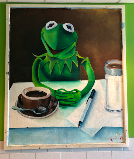 The painting by Elis F., created in 1993, depicts Kermit the Frog sitting at a table with a cup of tea and a jar of sugar directly in front of him.
