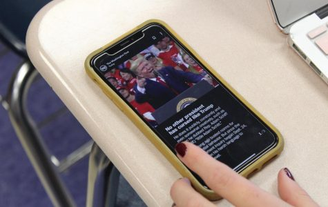 A student uses their phone to read The Washington Post.